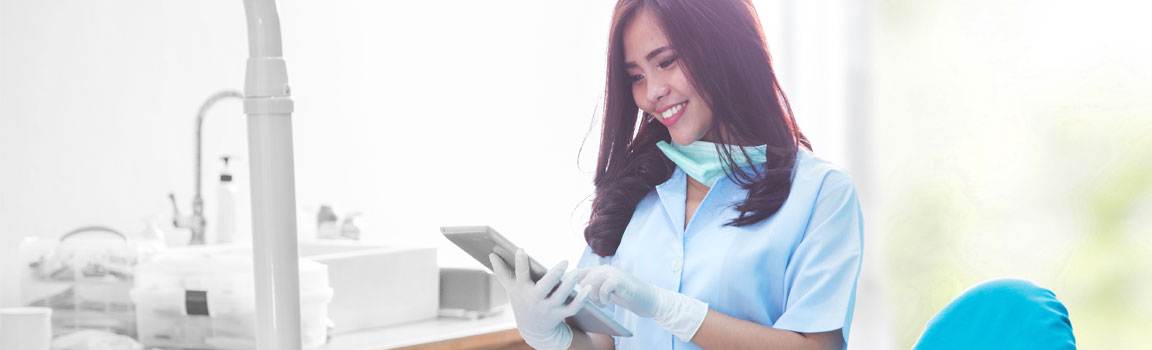 A female dentist is using a tablet in a dental clinic